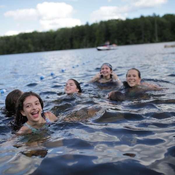 Group of female swim team members in the camp lake