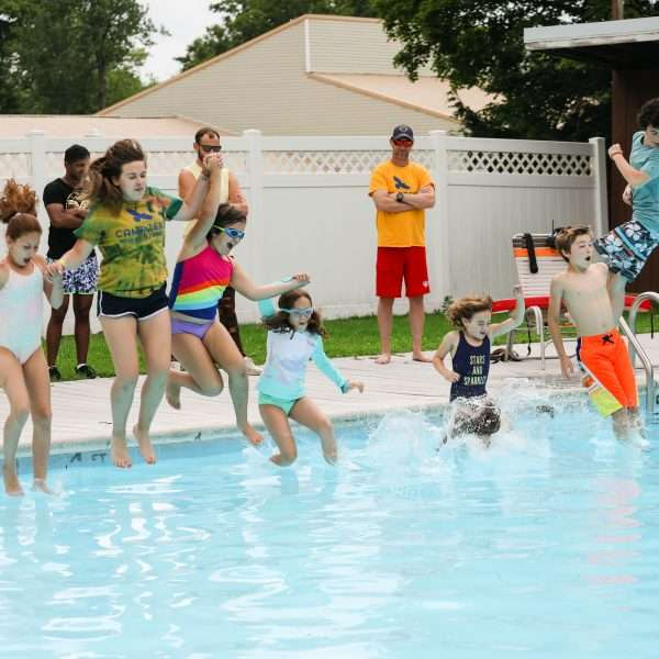 Group of campers jumping into the pool